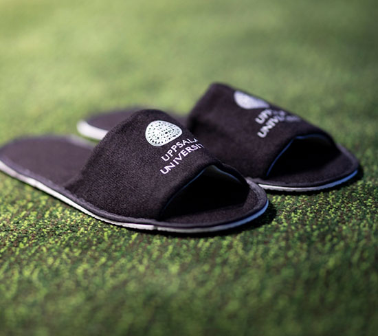 Black slippers with Uppsala University's logo in white. Photo.